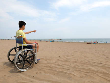 young boy with yellow vest on the wheelchair at beach in summer