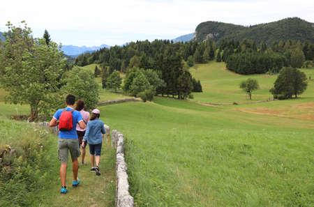 Familie mit zwei Kindern auf dem Weg in den Bergen