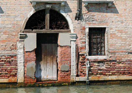 old wooden door on the canal in Venice Italy