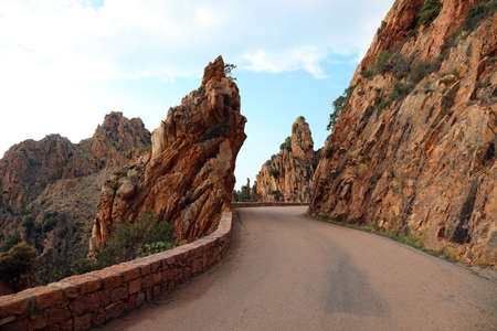 Narrow road called D81 in Corsica France and the red rocks called Calanches 版權商用圖片