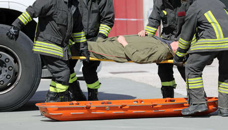 four firemen charge a wounded person on a stretcher after an accident