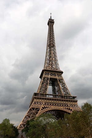 Eiffel Tower in Paris and the trees with cloudy sky 스톡 콘텐츠