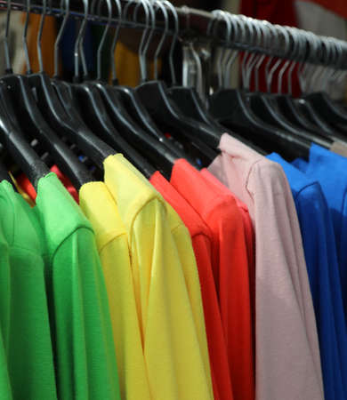 many colorful shirts hanging on the hanger for sale in the shop Stok Fotoğraf