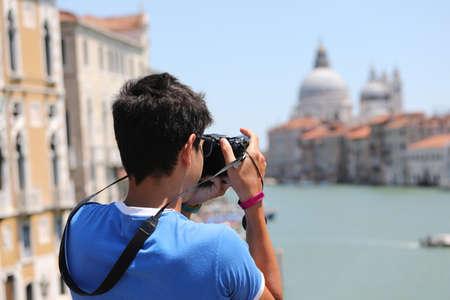 boy photographs the Basilica of the Madonna della Salute in Venice Imagens