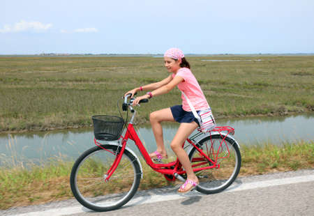 pretty little girl with pink hat on the bike in summer