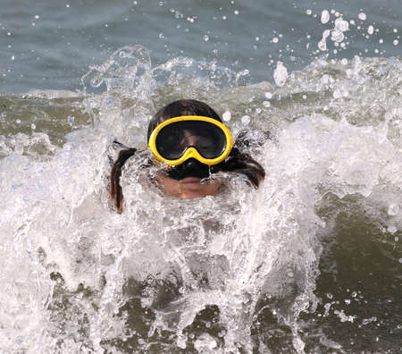 little girl plays with her diving mask on the sea Stock fotó