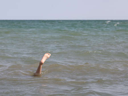 single foot in the middle of the sea of the person who is under water even with the head Stock Photo