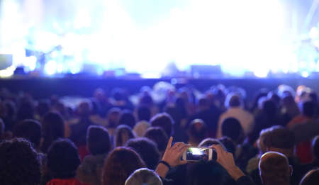 heads of people at concert and many spotlights on stage and a fan with smarthphone