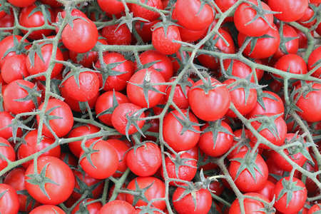 background of many red cherry tomatoes for sale