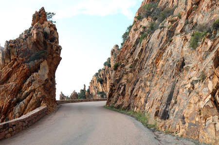 Narrow road and the badlands called Les  Calanches on the Corsica Island in France