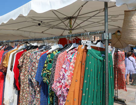 stand with many dress and clothes for sale at open air market