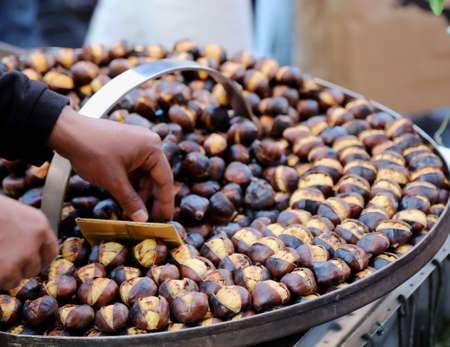 roasted chestnuts for sale on the stand on the street