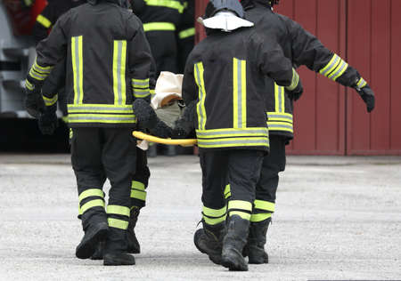 four firefighters carrying injured after the road accident Reklamní fotografie