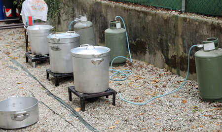 outdoor kitchen with many big cauldrons without people