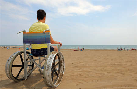 disabled boy sitting in a wheelchair gaze at the sea from the beach