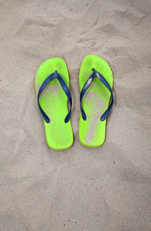two green flip flops on the sand beach of the sea during summer vacations