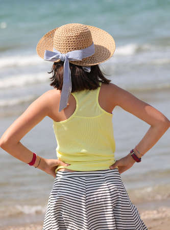 young girl with straw hat by the sea in summer