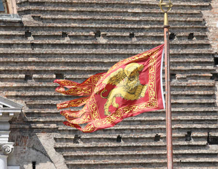 Veneto Region Flag also called Flag of Serenissima Repubblica with winged lion and the wall of bricks in background