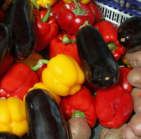 Eggplants and yellow and red peppers adn potatoes for sale