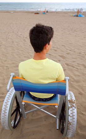 young boy on the special  wheelchair looks at the sea from the sandy beach in the summer 写真素材