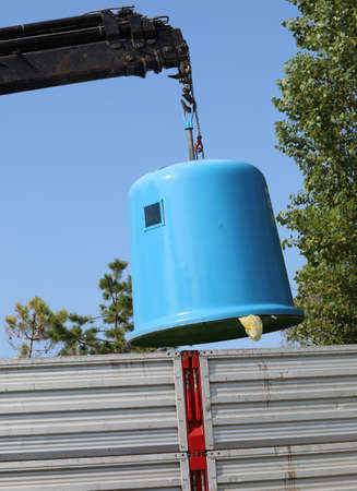 blue waste glass recycling container and the crane
