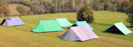 camping with many big tents on the meadow in autumn