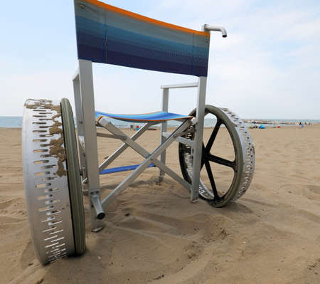 special wheelchair with wide wheels to move on the sandy beach without people by the sea