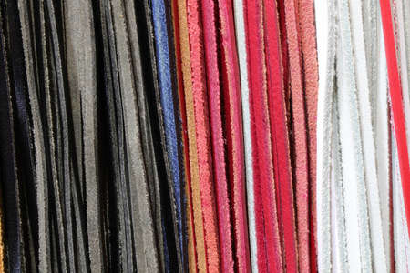 many strings of leather for sale at workshop of craftsman Stock Photo
