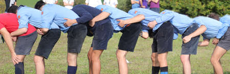 many boy with scout uniform playing at leapfrog outdoor in summer Stockfoto