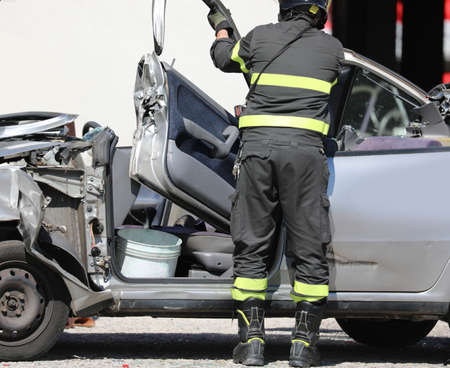 firefighters opens the damaged car after the road accident and the broken door