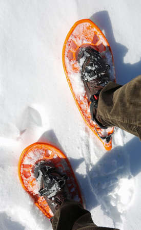 Man with corduroy pants with snowshoes on the white snow