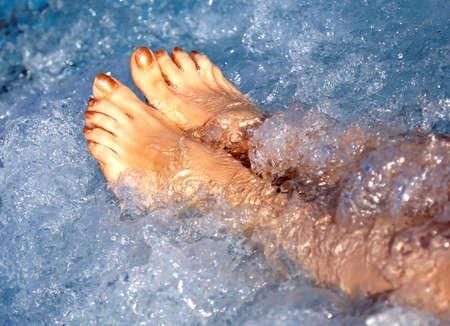 pieds de femme dans la piscine thermale et le bain à remous