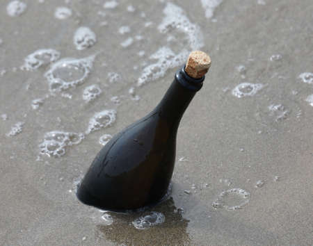 sea and a beached bottle of glass with a secret message 版權商用圖片