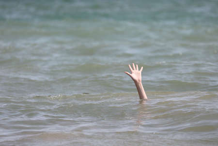 boy asking SOS on the sea with his hand