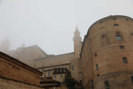 ancient tower of Ducal Palace with fog in Urbino town in Central Italy in the Marche Region Stock Photo