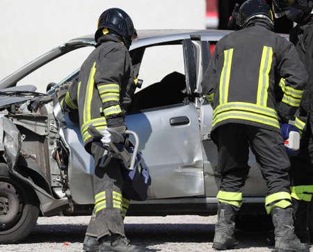 team van brandweerlieden opent de beschadigde auto na het verkeersongeval Stockfoto