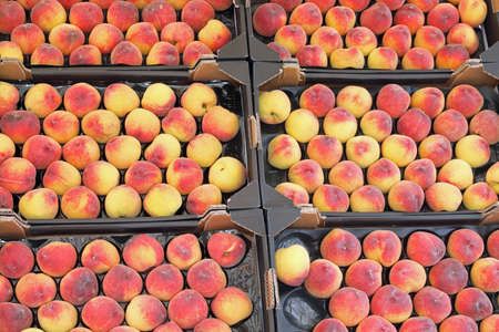boxes of peaches for sale at grocery store in summer