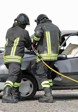 firefighters use a shear to open the door of a damaged car