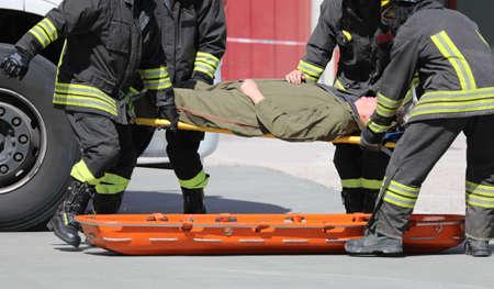 Equipo médico de cuatro camilleros que transportan a una persona lesionada tras el accidente de tráfico