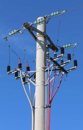 big pole with power line and the breaker or switch to open the circuit and blue sky on background