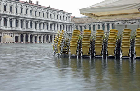 Yellow chairs in Saint Mark Square in Venice during awesome high tide