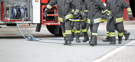 four firemen stretcher bearer after the road accident on the street and the fire engine