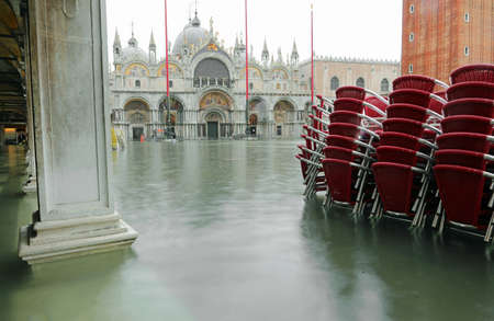 Red chairs in Saint Mark Square in Venice during awesome high tide with shooting with long exposure technique
