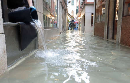 Street of Venice called CALLE in Italian language with high water and a bucket to empty the store Imagens