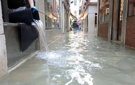 Via di Venezia chiamata CALLE in lingua italiana con acqua alta e un secchio per svuotare il negozio