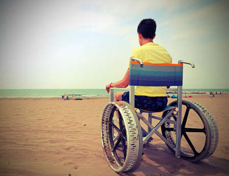 boy on a wheelchair looks at the sea from the beach Imagens