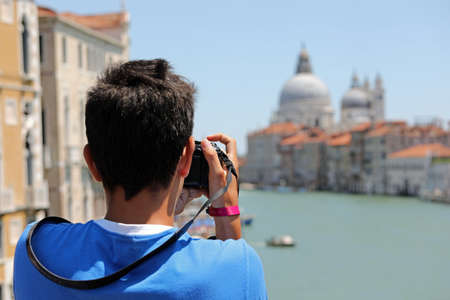 young boy takes pictures at Basilica called Madonna della Salute in Venice in Italy