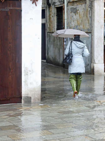 Woman with umbrella and big boot during the flood in Venice in Italy