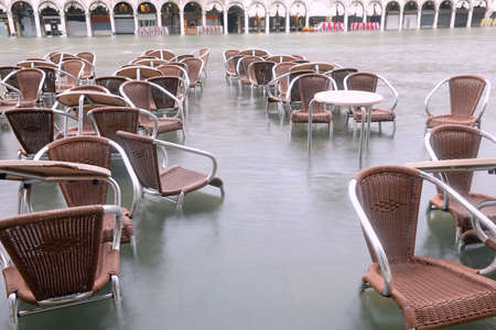 chairs on the water of Adriatic Sea in Main Square of Venice in Italy during the high tide