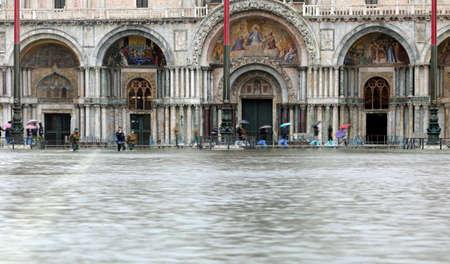 Acqua in piazza San Marco e persone sulle passerelle a Venezia in Italia Archivio Fotografico